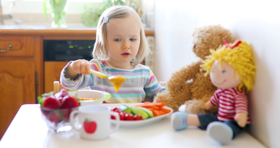 Adorable toddler girl eating fresh fruits and vegetables for lunch. Child feeding doll and teddy bear in the kitchen. Delicious healthy food for kids Royalty-Free Stock Footage #1048684741