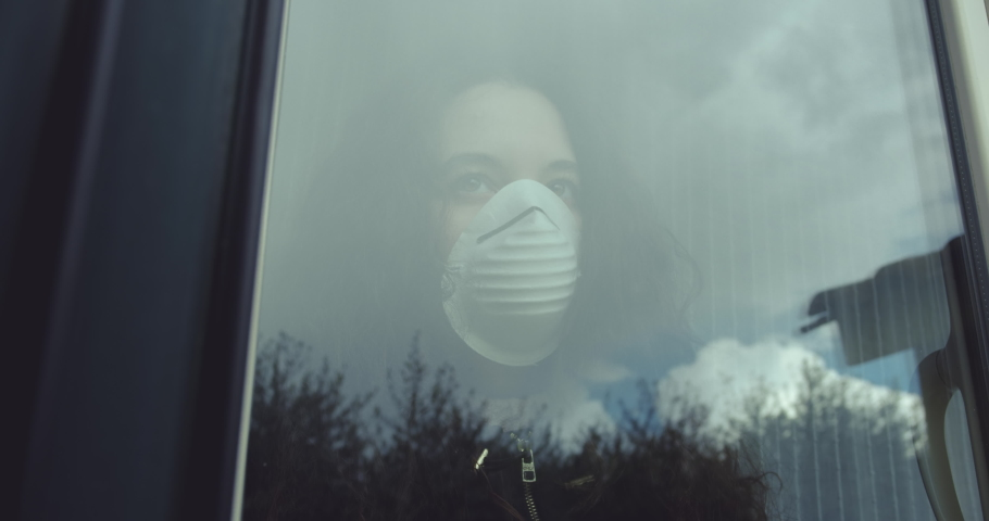 Pensive young woman wears a mask to protect herself from covid-19 while looking out the window. a bird in flight is reflected on the window glass