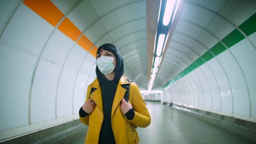 Adaptation to life in self-isolation COVID 19. Empty public transport hub, woman moves from work between metro stations in evening. Citizens adhere to prescribed rules on the ban of free movement. Royalty-Free Stock Footage #1048686898