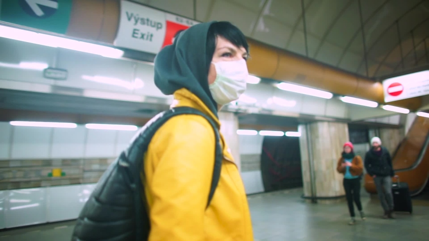 Adaptation to life in self-isolation COVID 19. A volunteer in a medical mask walks along the public transport station. Evacuation of tourists. Quarantine in Europe. Civil solidarity. | Shutterstock HD Video #1048686931