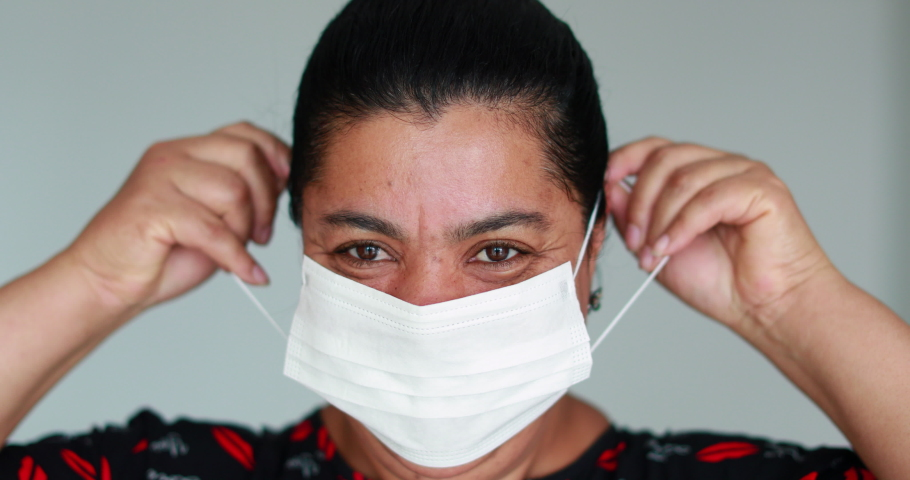 Black woman putting on face mask against virus bacteria prevention outbreak. African american descent woman wearing covid-19 mask | Shutterstock HD Video #1048692868