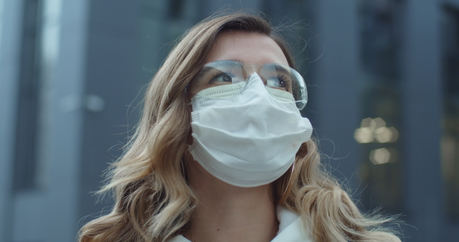 Young woman takes off medical mask. Breathes deeply and smiling looking at camera. isolated on white background. Health care and medical concept. Stay at home, quarantine | Shutterstock HD Video #1048701058