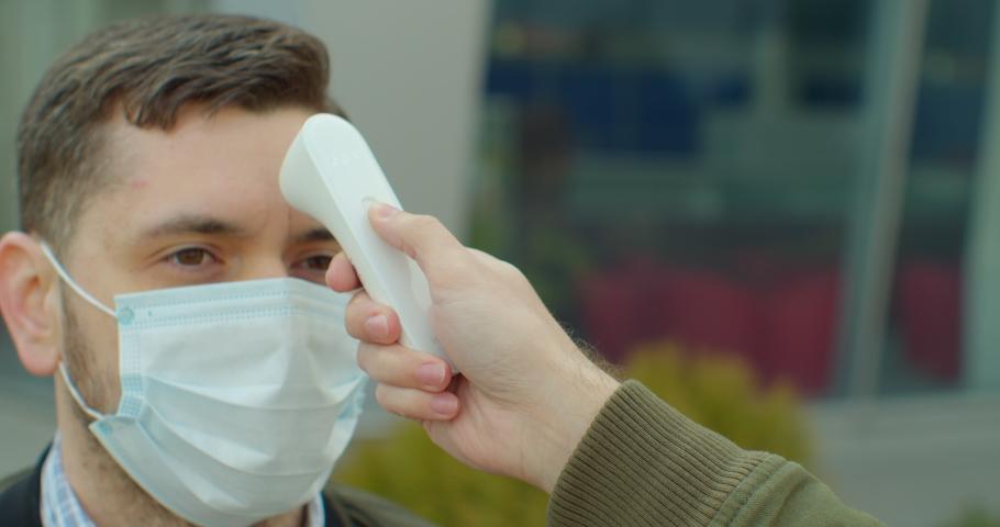 COVID-19 Body temperature measuring for coronavirus. A man's temperature is taken for controlling disease. | Shutterstock HD Video #1048707043