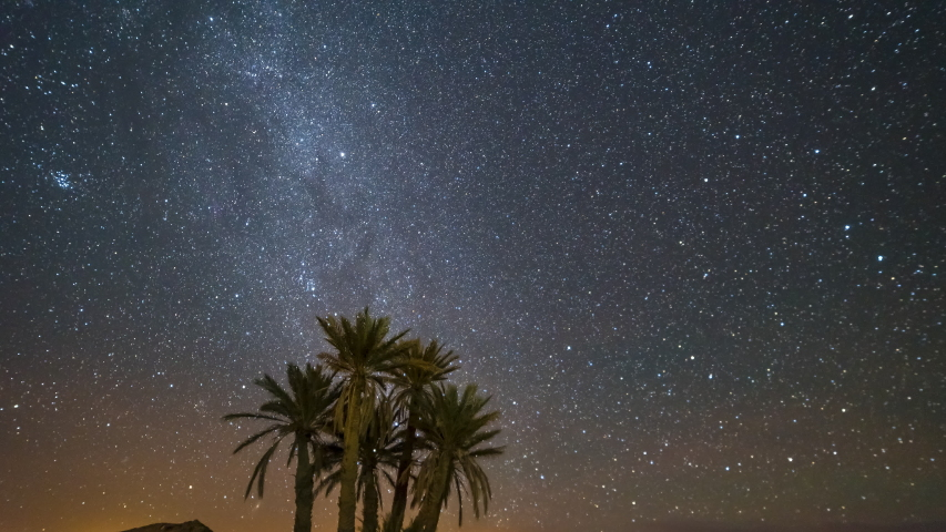 Incredible location in the middle of the desert surrounded by palm trees in Merzouga, Morocco making a timelapse video of the milky way in an amazing dark night till the moon rise at the end.
