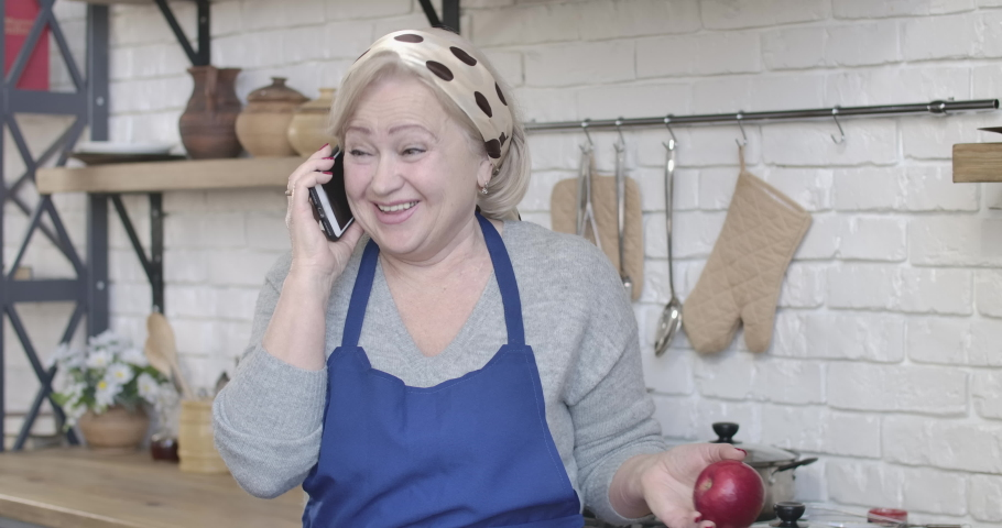 Portrait of cheerful female retiree eating apple and talking on the phone. Joyful blond Caucasian woman laughing as chatting in kitchen at home. Leisure, retirement, lifestyle. Cinema 4k ProRes HQ.