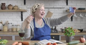 Portrait of laughing senior Caucasian woman posing with whisk and wineglass at selfie camera. Mature positive retiree having video call on smartphone. Cinema 4k ProRes HQ.
