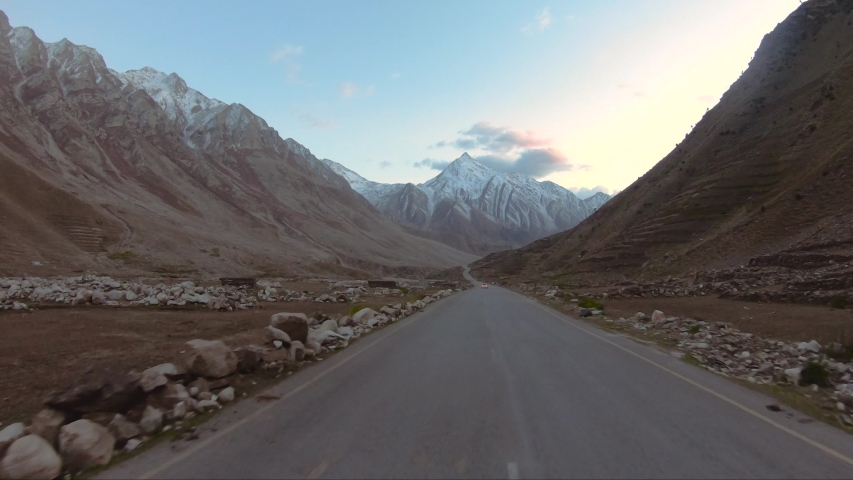 Driving car on Karakoram highway Pakistan mountains road in autumn having brown color mountains on both sides