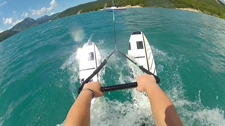 POV view of waterskiing. Water ski action camera, hands hold rope. Summer sports at blue water lake. Wakeboarding behind the motorboat. Concept of active lifestyle.