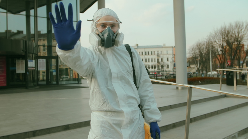 Man, worker disinfects against coronavirus, makes stop sign with hand, saying no, expressing restriction. Sanitary measures in public place during quarantine. Slow-mo | Shutterstock HD Video #1048749655