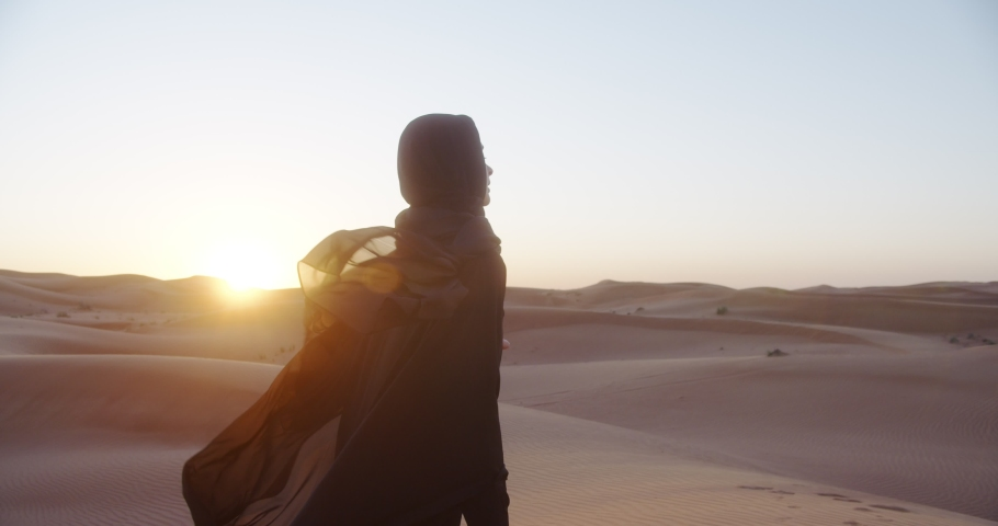 Beautiful girl in traditional Abaya dress and in hijab enjoys nature in the desert at sunset. 4K Slow Motion