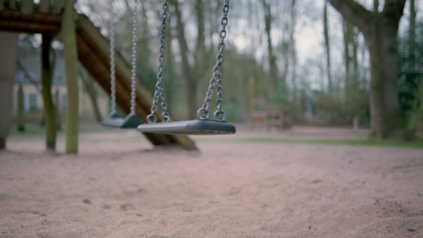 Empty swing on children playground during state of emergency by the reason of covid-19 virus threat Royalty-Free Stock Footage #1048753363