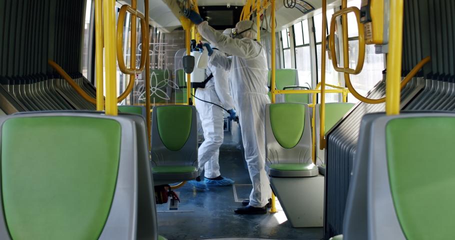 HazMat team in protective suits decontaminating public transport tourist bus interior during virus outbreak. Coronavirus, COVID-19 Royalty-Free Stock Footage #1048756120