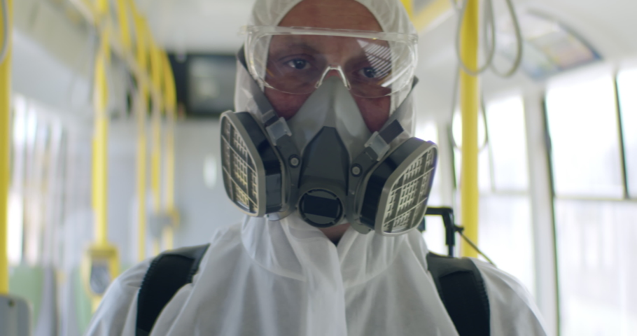 Portrait of HazMat team member in protective suits posing a bus during virus outbreak. Coronavirus, COVID-19 Royalty-Free Stock Footage #1048763092