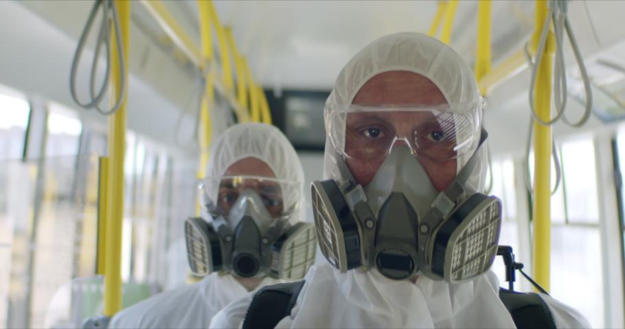 HazMat team in protective suits decontaminating public transport tourist bus interior during virus outbreak. Coronavirus, COVID-19 Royalty-Free Stock Footage #1048763107
