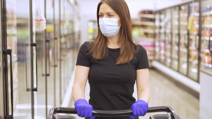 Woman shopping in grocery store for food while wearing PPE and preventing spread of virus germs by wearing face mask and latex gloves | Shutterstock HD Video #1048764802