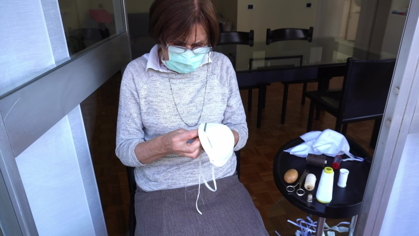 Europe, Italy, Milan - 70 year old lady with quarantine mask at home to protect herself from the epidemic n-cov19 Coronavirus makes domestic activity - sew and repair the mask anti-virus Royalty-Free Stock Footage #1048767949