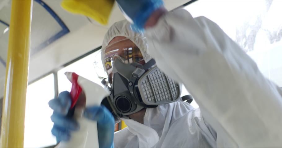 HazMat team in protective suits decontaminating public transport tourist bus interior during virus outbreak. Coronavirus, COVID-19 Royalty-Free Stock Footage #1048772542