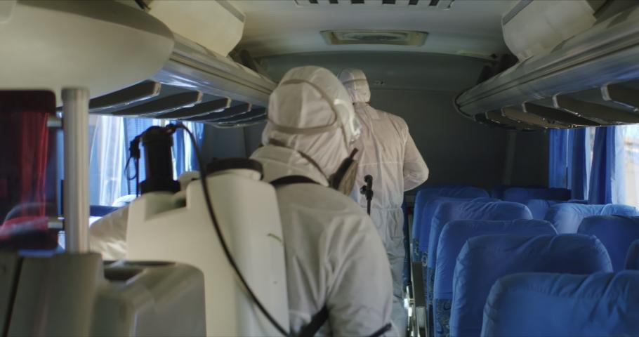 HazMat team in protective suits decontaminating public transport tourist bus interior during virus outbreak. Coronavirus, COVID-19 Royalty-Free Stock Footage #1048772545