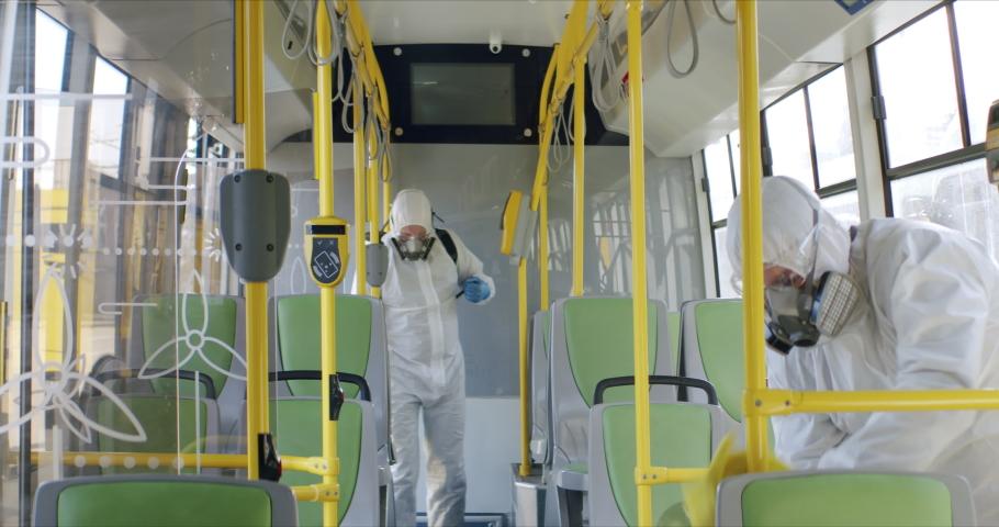 HazMat team in protective suits decontaminating public transport tourist bus interior during virus outbreak. Coronavirus, COVID-19 Royalty-Free Stock Footage #1048772548