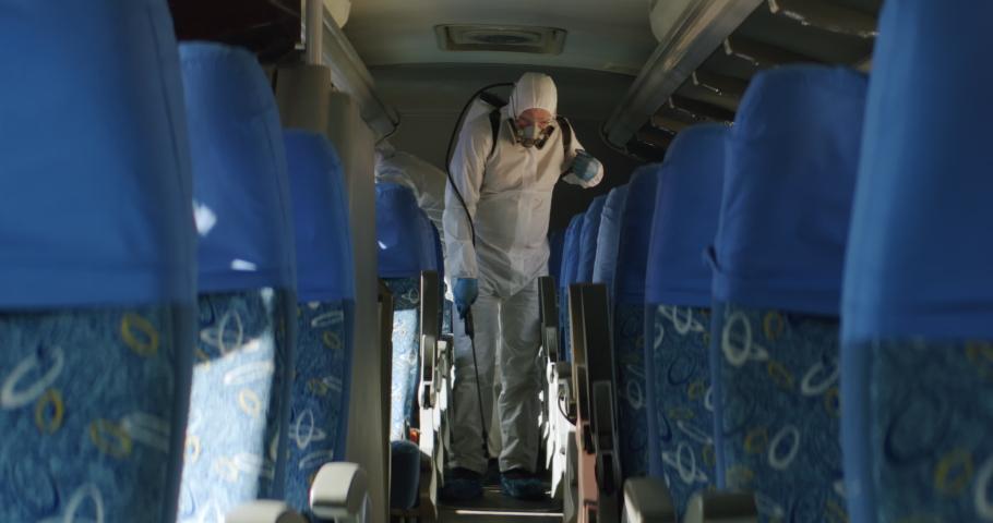 HazMat team in protective suits decontaminating public transport tourist bus interior during virus outbreak. Coronavirus, COVID-19 Royalty-Free Stock Footage #1048772554