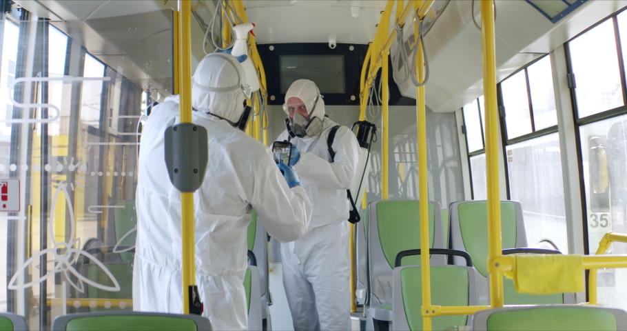 HazMat team in protective suits decontaminating public transport, bus interior during virus outbreak Royalty-Free Stock Footage #1048772557