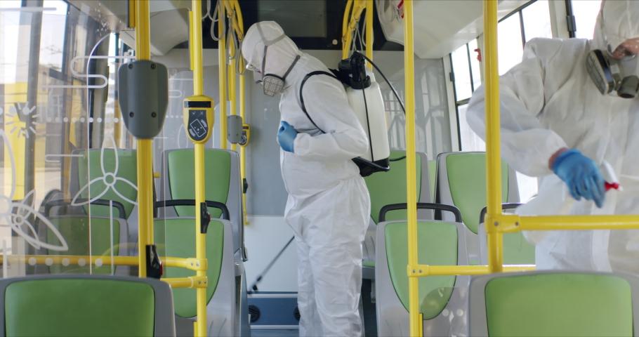 HazMat team in protective suits decontaminating public transport, bus interior during virus outbreak Royalty-Free Stock Footage #1048772560