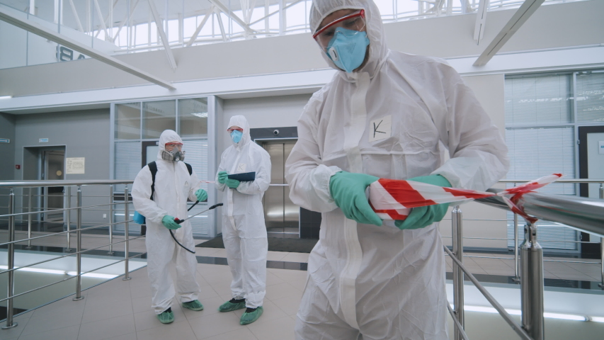 Covid-19 protective measures. Scientists in protective coveralls and masks securing biohazard place with barrier tape before disinfection. Team of workers disinfecting and cleaning business center | Shutterstock HD Video #1048778128