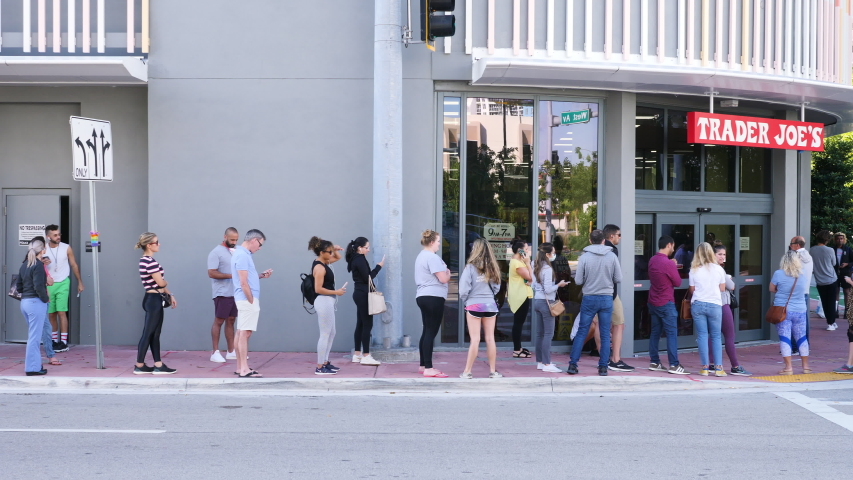 Miami, USA - March 19, 2020: People waiting in line outside grocery store before opening as they want to get in first and purchase goods before products are sold out due to covid-19 coronavirus