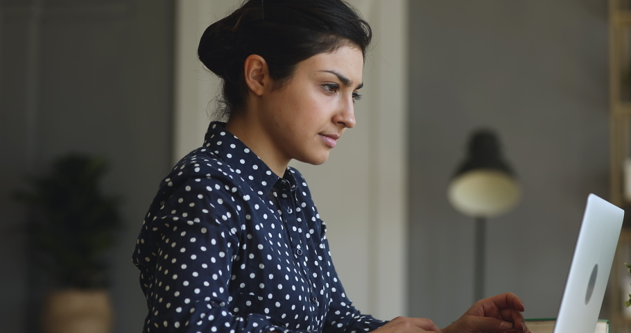 Side view concentrated young indian businesswoman working on computer at office or home, communicating with clients. Focused successful hindu female international company employee busy with project. Royalty-Free Stock Footage #1048785208