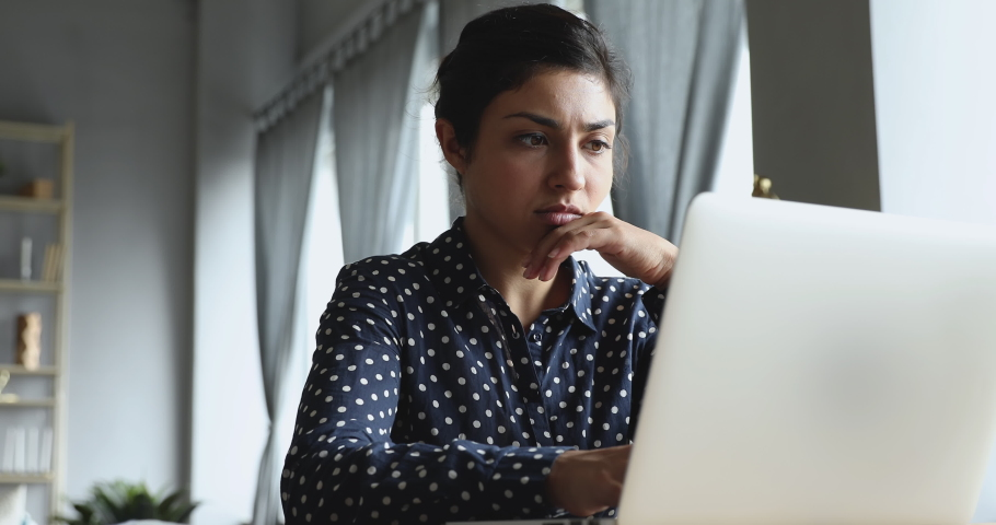 Focused young indian woman looking at computer monitor. Concentrated entrepreneur freelancer working remotely on laptop online at home office, solving problems. Serious student doing homework. Royalty-Free Stock Footage #1048785235