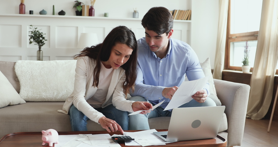 Young couple calculating bills, taxes and expenses, counting mortgage rate making savings concept. Millennial husband and wife considering taking bank loan, investing money. Family financial economy. Royalty-Free Stock Footage #1048785283