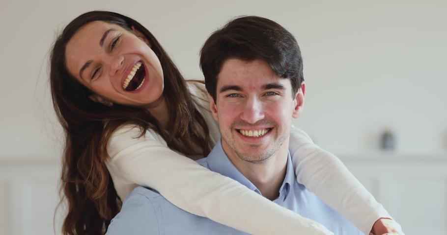Young couple home owners with dental smiles laughing, having fun together looking at camera. Happy adult guy piggybacking pretty girl indoor. Mortgage investment, dentistry concept. Close up portrait