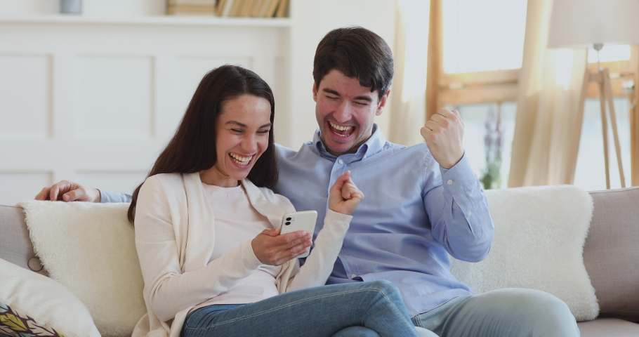 Excited young couple winning giveaway lottery prize in social media app online on smartphone. Happy euphoric millennial man and woman winners celebrating success holding mobile phone sitting on sofa. Royalty-Free Stock Footage #1048785430