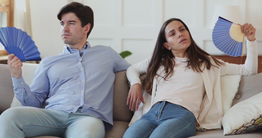 Unhappy frustrated couple suffering from heat, bad air conditioning at home waving fans sitting on sofa. Overheated young man and woman sweating feeling hot and dehydrated in summer swelter concept. | Shutterstock HD Video #1048785442