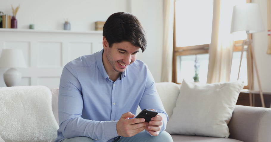 Smiling millennial man using smart phone sitting on sofa in living room. Happy young male user texting sms message, playing game or chatting in internet social media dating mobile modern app at home. Royalty-Free Stock Footage #1048785469