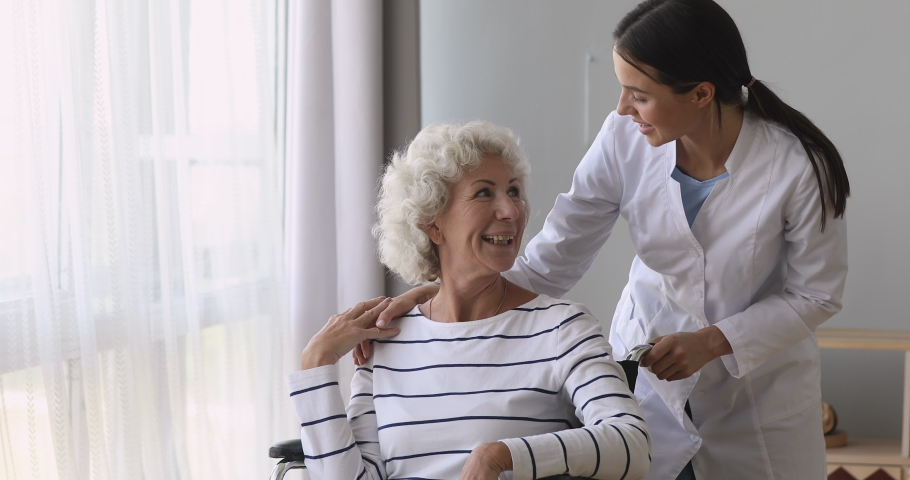 Pleasant young caregiver volunteer medical worker talking to smiling disabled 70s woman in wheelchair. Professional nurse female doctor supporting retired elderly patient at home or retirement house.