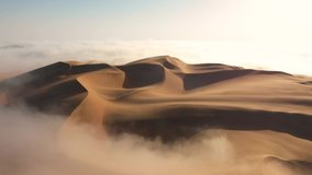 Aerial view of a drone flying over massive sand dunes covered by thick fog clouds at sunrise. Liwa desert, Abu Dhabi, United Arab Emirates.