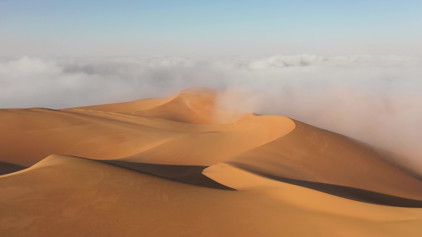 Aerial view of a drone flying over massive sand dunes covered by thick fog clouds at sunrise. Liwa desert, Abu Dhabi, United Arab Emirates. | Shutterstock HD Video #1048792483