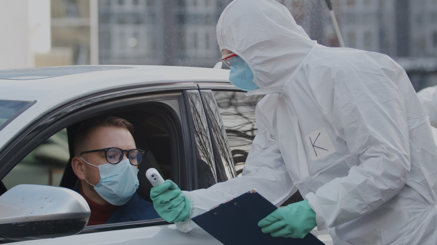 Prevent coronavirus pandemic outbreak. Doctors in hazmat suits checking body temperature of car driver traveller in facial mask and disinfecting his car with detergent spray before letting him drive