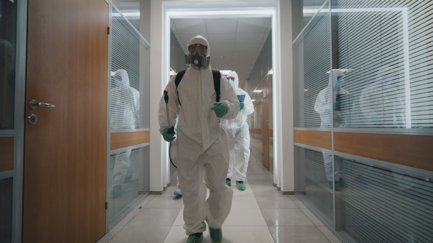 Fighting covid-2019 three men in protective suits carrying equipment and examining building after disinfection against coronavirus. Specislists disinfecting empty office during coronavirus quarantine