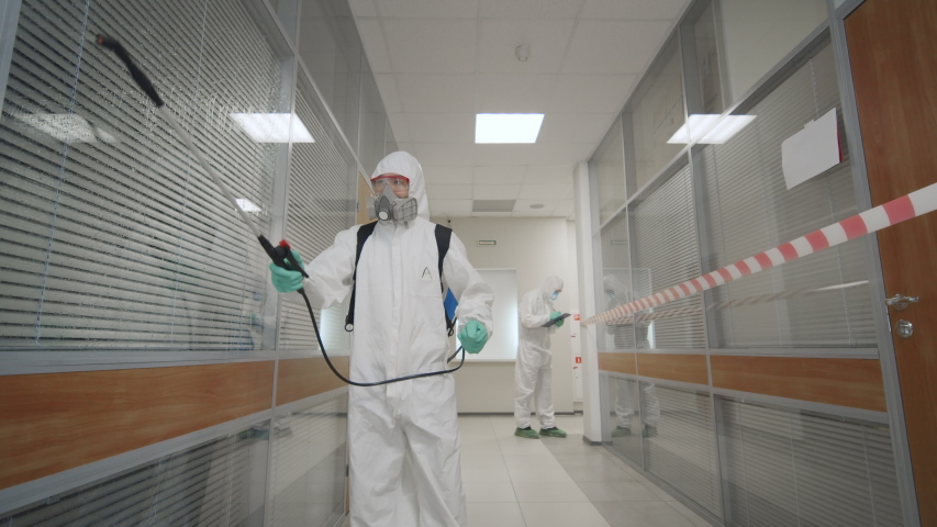 2019-ncov spreading, coronavirus outbreak. Team of virologists in protective coveralls and masks working in office building disinfecting rooms fighting against coronavirus spread. Royalty-Free Stock Footage #1048795996