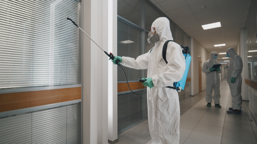 Covid-19 spreading. Workers in hazmat suits and respirator masks sprays disinfectant in office building as part of preventive measures against the spread of the coronavirus | Shutterstock HD Video #1048796008
