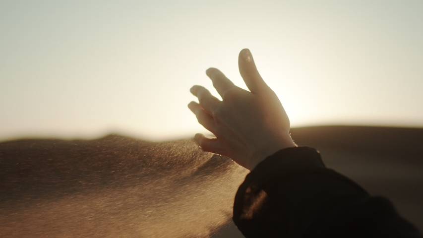 Close-up hand signs with handful of sand. Sand from the desert spills out of the girl's hand. 4K Slow Motion