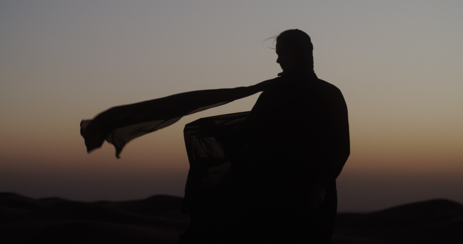 In the Dubai desert at sunset, girl in the wind develops traditional Abaya dress and hijab. 4K Slow Motion