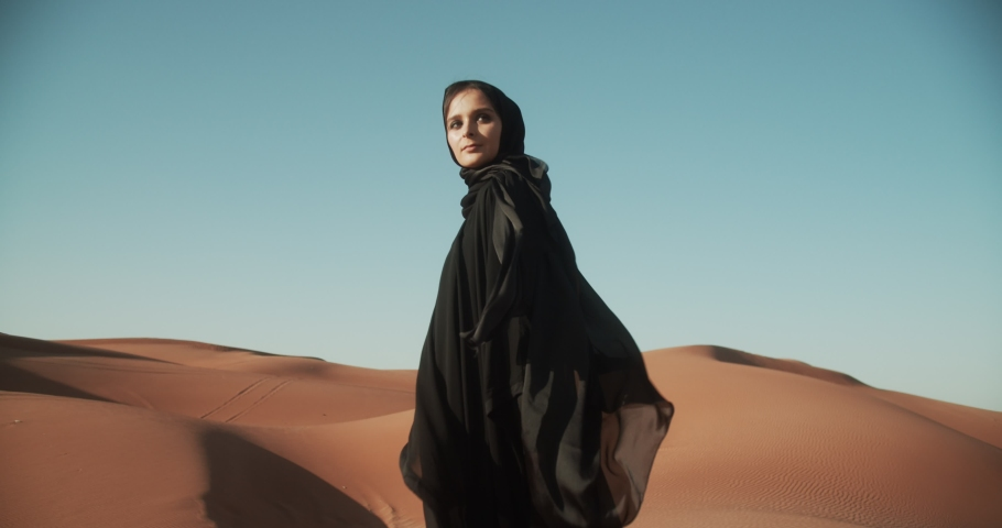 Young beautiful girl in traditional Abaya dress walks along the dunes in the desert of Dubai. 4K Slow Motion