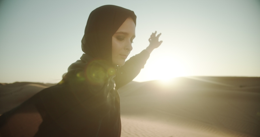 Arab girl in hijab and abaya in the desert at sunset holds sand in her hands. 4K Slow Motion
