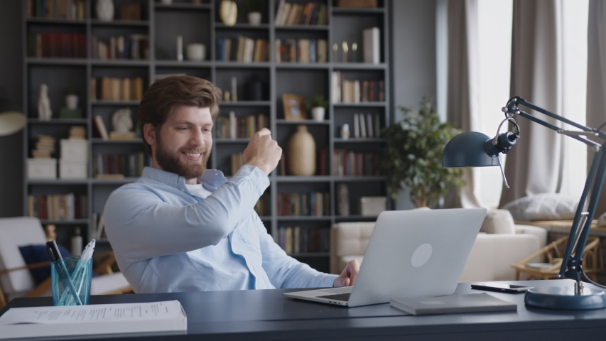young business man sits at table with a laptop working in home office. He gets great news and is delighted. clicks fingers and says yes. leans back of the chair and smiles Royalty-Free Stock Footage #1048801462