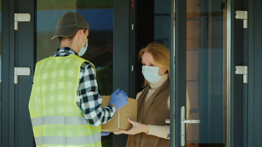 A courier wearing a mask and protective gloves delivers a parcel. Working in a pandemic
