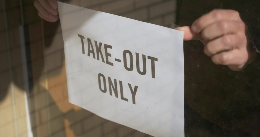 A cafe owner puts a TAKE OUT ONLY sign on the front door. Take out or carry away quickly became the only option for restaurants and bars during the coronavirus COVID-19 pandemic of 2020.