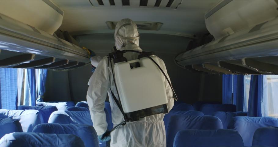 HazMat team in protective suits decontaminating public transport tourist bus interior during virus outbreak. Coronavirus, COVID-19 Royalty-Free Stock Footage #1048813864